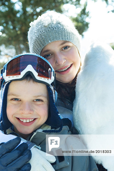 Brother and sister smiling at camera  cheek to cheek  dressed in winter clothing  portrait