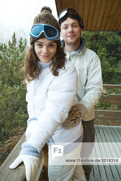 Junges Paar auf dem Balkon stehend  in Winterkleidung gekleidet  lächelnd vor der Kamera