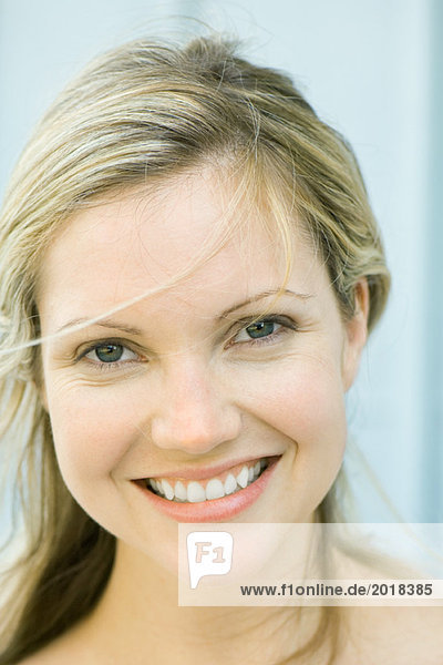 Junge Frau lächelt vor der Kamera  zerzaustes Haar  Portrait