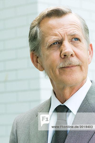 Senior Geschäftsmann schaut nach oben  Porträt