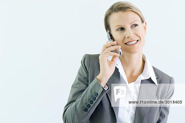 Geschäftsfrau mit dem Handy  lächelnd  wegschauend