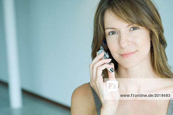 Woman using cell phone  looking at camera  portrait