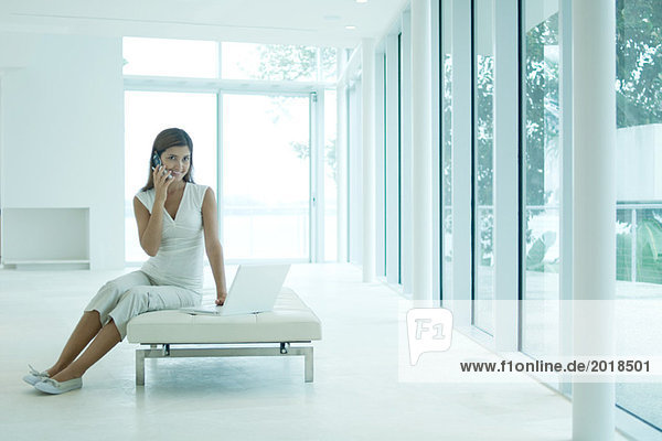 Junge Frau auf dem Sofa sitzend  mit Handy und Laptop  lächelnd