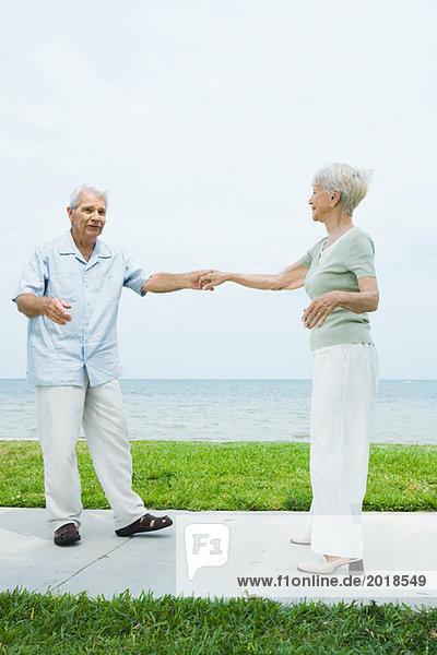 Senior couple dancing on sidewalk overlooking ocean  full length