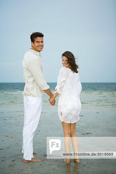 Mann und junge Begleiterin am Strand  Händchen haltend  über die Schultern blickend  volle Länge