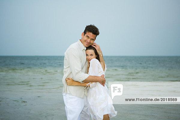 Mann und junge Begleiterin am Strand  umarmend  in die Kamera schauend