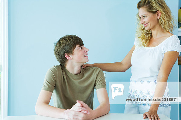 Woman standing next to teen son sitting at table  hand on his shoulder  both smiling at each other