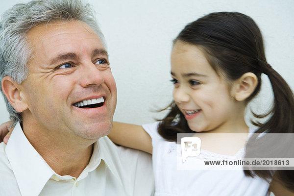 Kleines Mädchen mit Arm um den Mann  lächelnd  Mann lächelnd und wegschauend  Portrait
