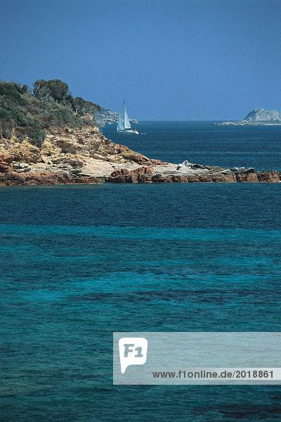Korsika  Segelboot entlang der Küste  türkisfarbenes Meer im Vordergrund