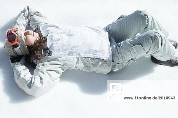 Teenage girl lying on snow  high angle view