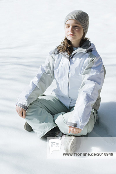Teenage girl sitting indian style on snow with eyes closed and head back  full length