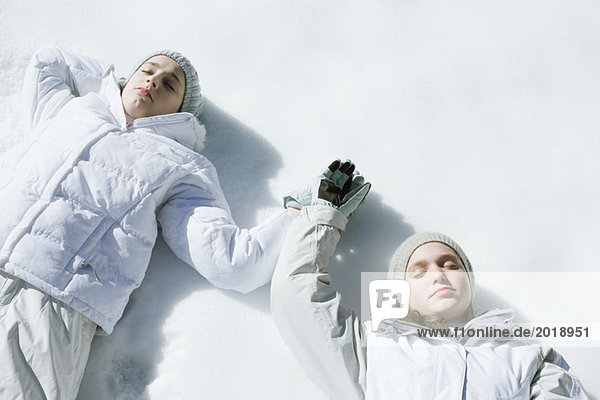 Teenage girls lying on snow with eyes closed  holding hands