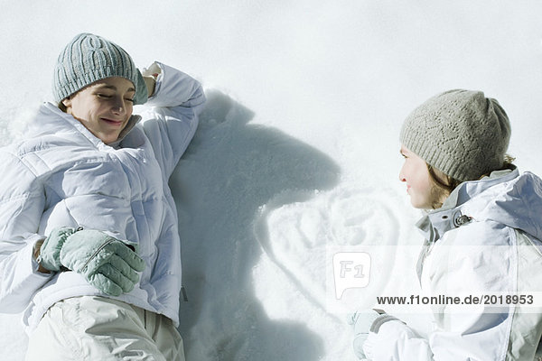 Teenage girls lying on snow  heart with initials drawn on surface of snow