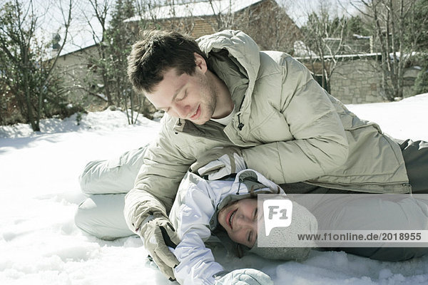Two friends roughhousing outdoors in snow