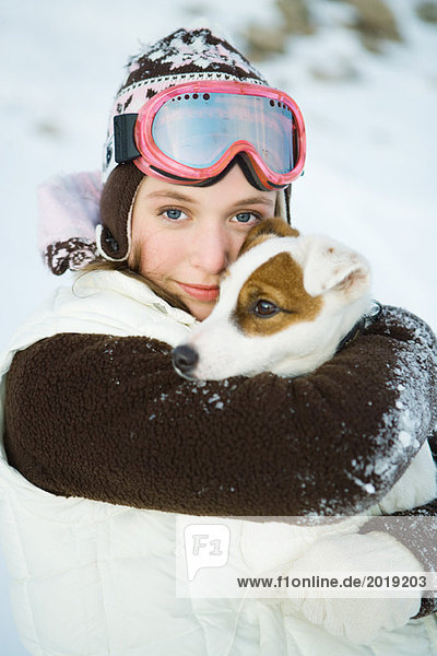 Teenage girl embracing dog  dressed in winter clothing  smiling at camera  portrait