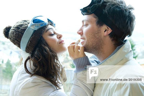Junge Frau  die Lipbalm auf die Lippen des Freundes aufträgt  beide in Winterkleidung  Seitenansicht  Mund