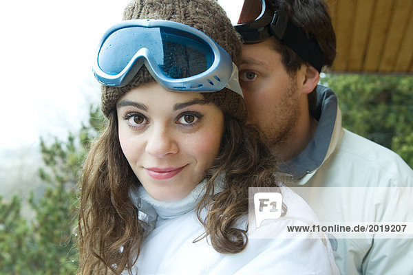 Young couple standing together  female smiling at camera  boyfriend peeking from behind