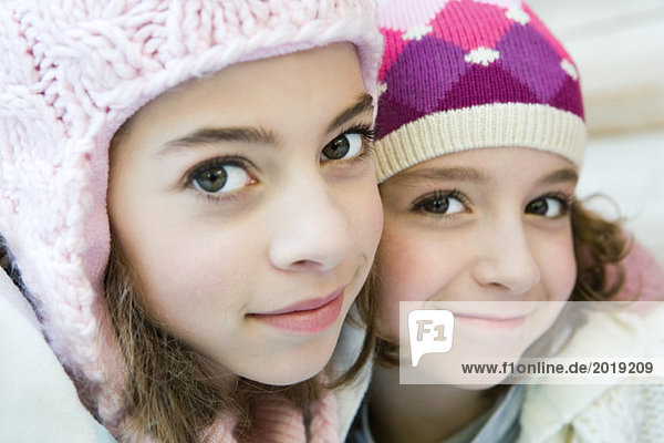 Two young sisters smiling at camera  both wearing knit hats  cheek to cheek  portrait