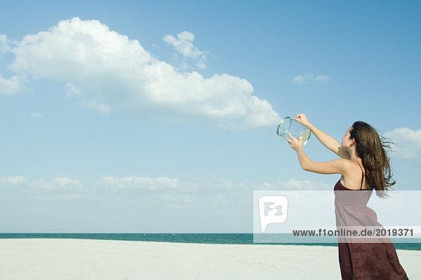 Frau steht am Strand  hält klaren Behälter hoch  löst Wolken  optische Täuschung