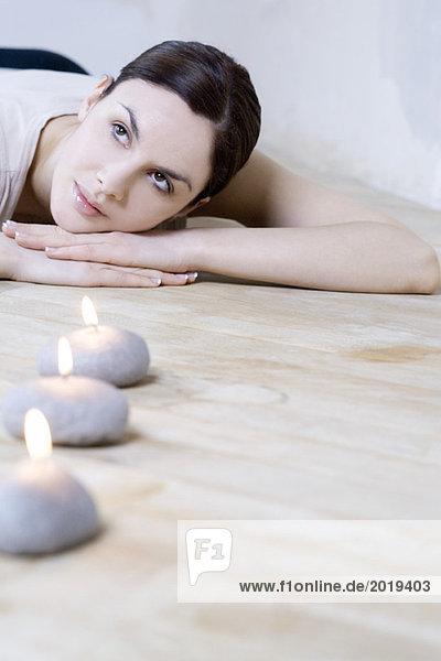 Junge Frau auf dem Bauch liegend  Kopf auf den Armen ruhend  brennende Kerzen im Vordergrund