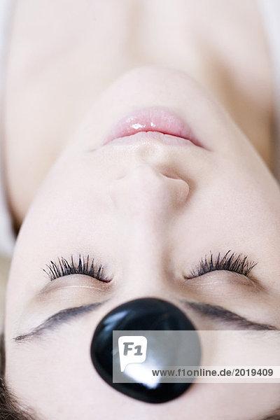 Junge Frau liegt mit Kieselstein auf der Stirn  Augen geschlossen  Nahaufnahme