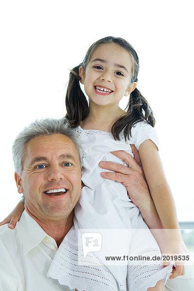 Mann hält kleines Mädchen hoch  beide lächelnd vor der Kamera  Porträt