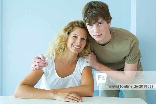 Teen boy standing next to mother sitting at table  cheek to cheek  smiling at camera  portrait