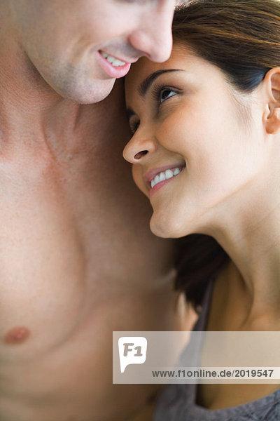 Junges Paar  Frau ruht Kopf auf der nackten Brust des Mannes  schaut zu ihm auf  Nahaufnahme