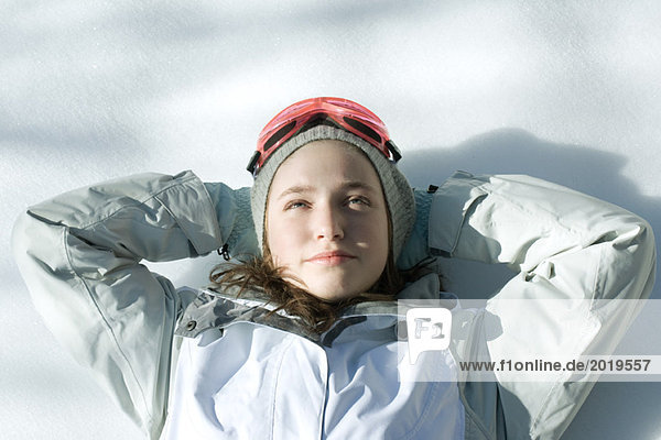 Teen girl lying on snow with hands behind head  head and shoulders