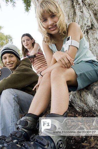14-15-Jahre,Audiozubehör,Baumstamm,Blick in die Kamera,Blondes Haar