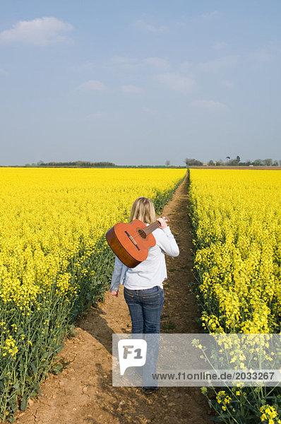 Frau im Feld mit Gitarre