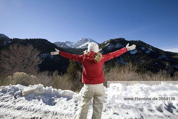 Eine Frau  die mit ausgestreckten Armen auf die Berge schaut.