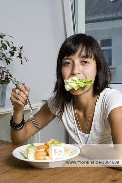 Eine Frau  die an einem Tisch sitzt und einen Salat isst.