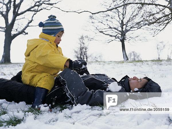Eine Mutter und ein Sohn spielen zusammen im Schnee.