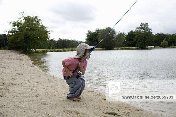 Ein Junge  der am Rande eines Sees fischt.