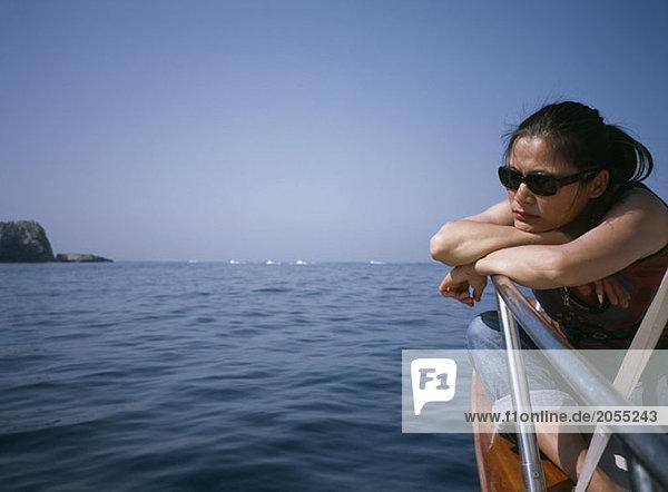 Eine Frau  die auf einem Bootsdeck sitzt und nachdenkt.