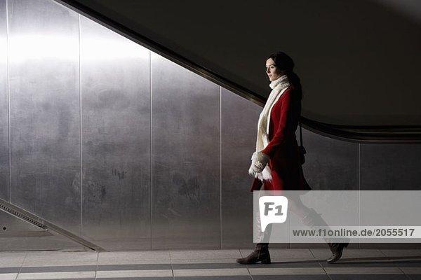 Eine Frau  die nachts an einer Rolltreppe vorbeigeht.