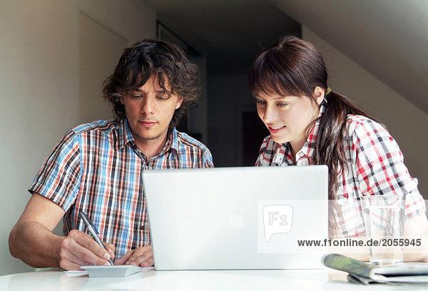 Mädchen und Kerl vor dem Computer