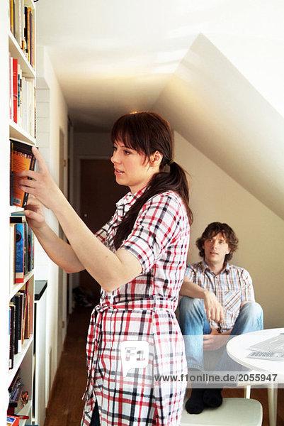 Frau bekommt Buch aus Bücherschrank