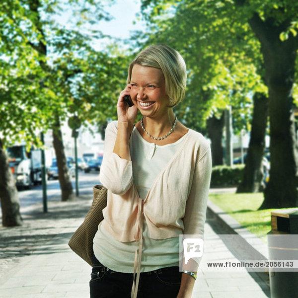 Junge glückliche Frau auf dem Handy