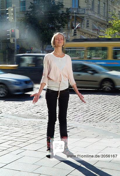 Junge Frau  die ihre Hände in der Stadt ausstreckt.