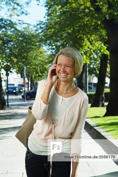 Junge Frau spricht auf ihrem Handy in der Innenstadt.