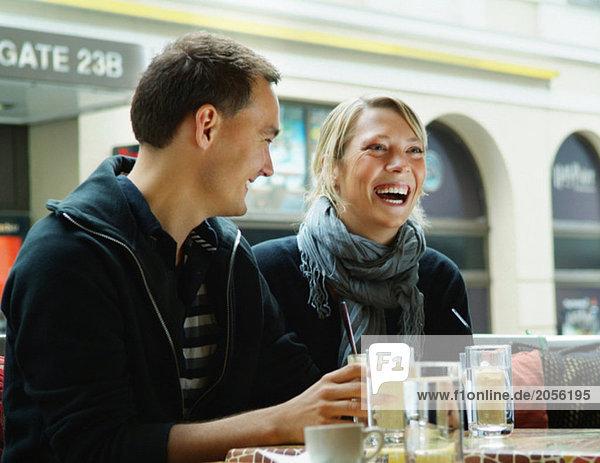 Mädchen und Kerl in einem Café lachend
