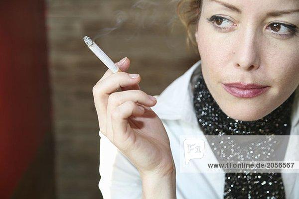 Eine Frau sitzt rauchend im Café