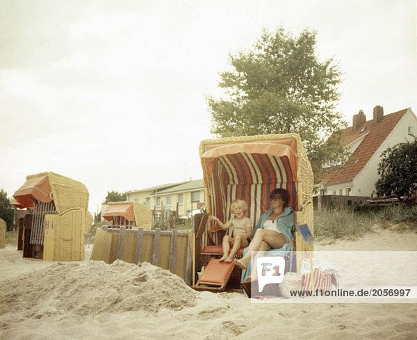 Mutter und Sohn im Sommer am Strand in einem Strandkorb