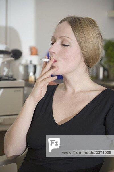 Frau  die in der Küche eine Zigarette raucht