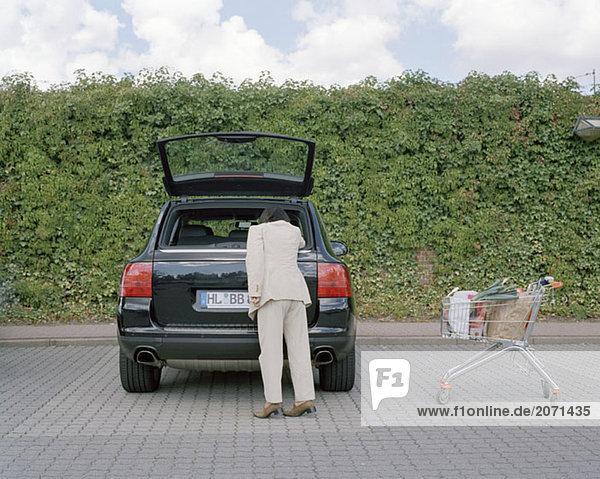 Frau reicht in einen Kofferraum hinein  Einkäufe aus einem Einkaufswagen verstauend