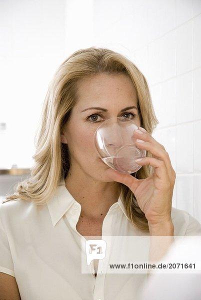 Eine Frau trinkt ein Glas Wasser