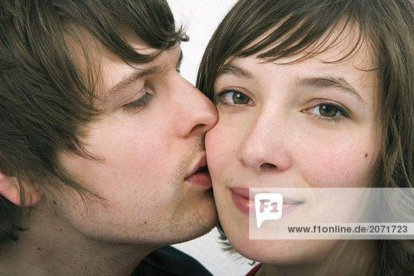 Ein junger Mann küsst eine junge Frau auf die Wange