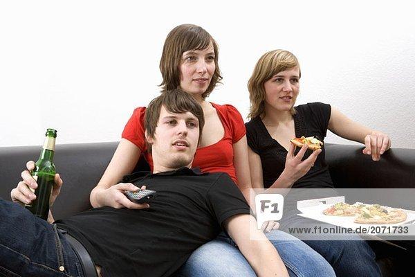 Drei junge Erwachsene sitzen gemeinsam auf dem Sofa  trinken Bier  essen Pizza und schauen fern.